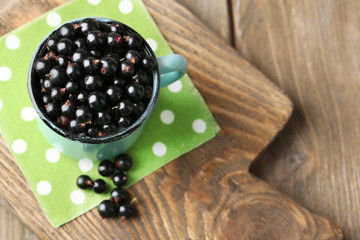 Ripe blackcurrants in mug on board, on wooden background.