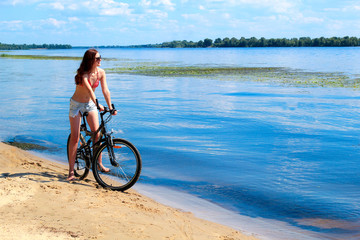 woman riding a bicycle on the river beach