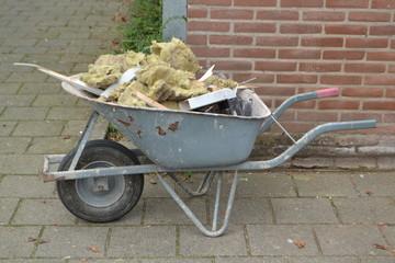 een kruiwagen met puin wordt afgevoerd