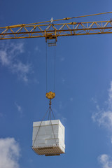crane lifting stacked white styrofoam sheets