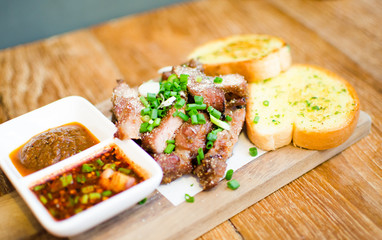 Slice Grilled pork with thai chilli sauce and garlic bread serve