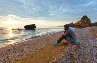 Woman on Potistika beach. Sunrise view (Greece)