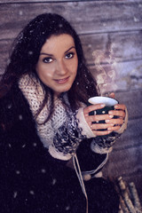 Beautiful girl with cup of hot tea on a winter day