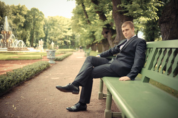Groom sit on the bench in a park