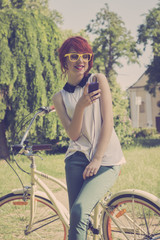 Hipster girl on her vintage bike, listening to the music. Retro