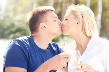 Adult couple kissing at the beach with champagne