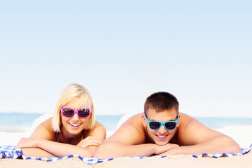 Young couple sunbathing at the beach
