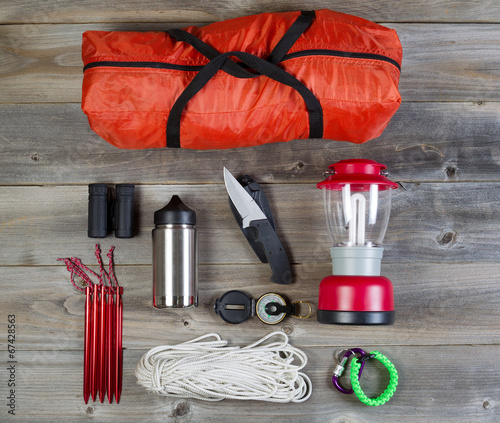 Camping Gear on Rustic Wooden Boards - 67428563