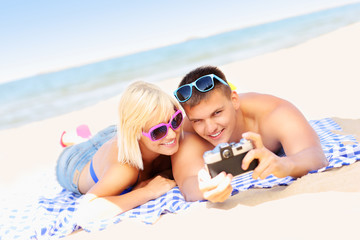 Young couple taking pictures at the beach