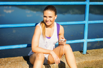 Pretty young runner woman with smartphone and headphones
