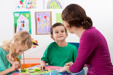 The teacher helps children