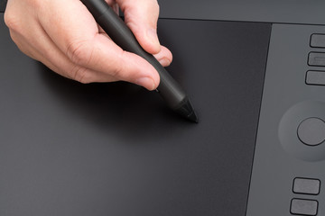 Hand Holding Graphic Pen Over Table