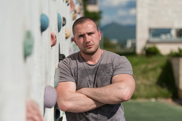 Man Stands In Front Of An Outdoors Climbing Wall