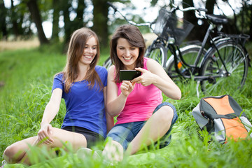 Girls with smartphone on a glade