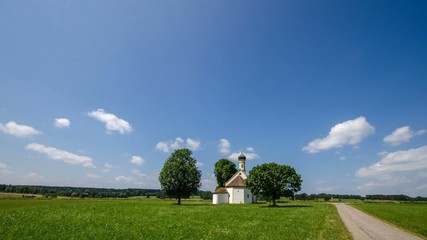 Timelap - weißblauer himmel über einer kleinen Kirche