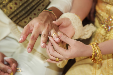 Thai bride wearing wedding ring for her groom hand