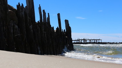 Old pier ruins, sandy beach, sea and blue sky