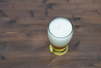 glass with beer on old wooden table
