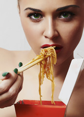 Beautiful woman are eating noodles.Chinese sticks.fast food