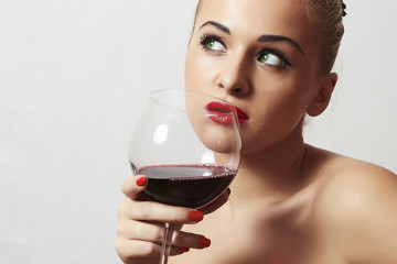Beautiful blond woman drinking red wine.make-up.red lips