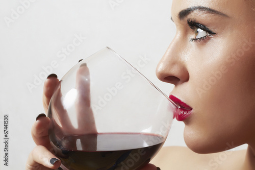 Beautiful blond woman drinking red wine.girl with wineglass