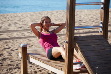 Attractive middle age woman doing abdominal crunches on beach