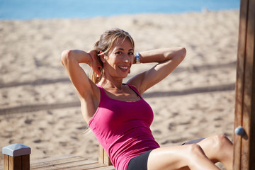 Woman doing abdominal crunches and smiling looking to camera