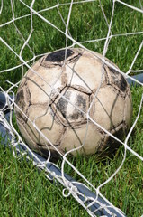 Old soccer ball in the goal net on green grass