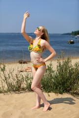 Dziewczyna, blondynka na plaży w stroju kąpielowym.