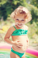 Smiling little girl in the swimming pool