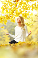 Woman meditating in autumn park
