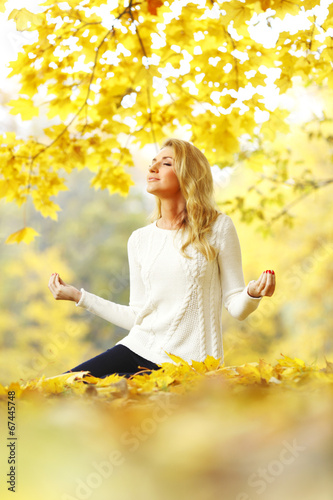 canvas print picture Woman meditating in autumn park