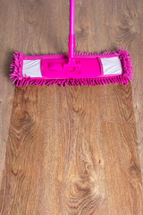 close up of wooden parquet floor with pink mop - before after