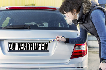 Woman writes with a brush on the sign of cars