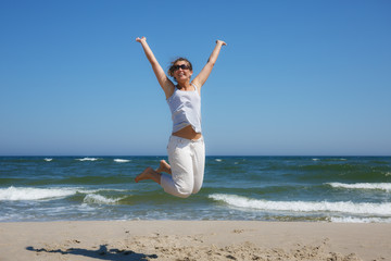 Woman in a jump shot on the beach of the Baltic sea in summer