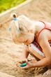little blonde girl playing in sandpit