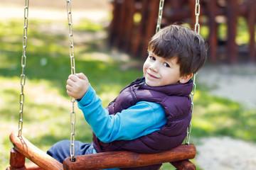 Little boy in winter waistcoat swinging