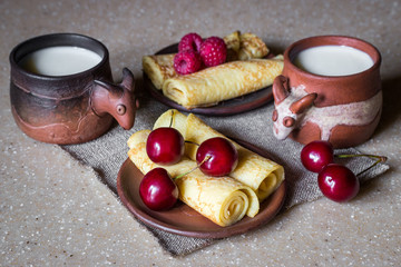 Breakfast of rolled pancakes with berries and milk, still life