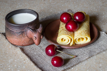 Breakfast of rolled pancakes with cherries and milk, still life