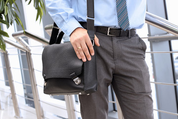 Businessman standing  and holding  a  leather briefcase on his s