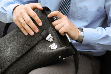 Businessman siting on a chair and opening  his   leather briefca