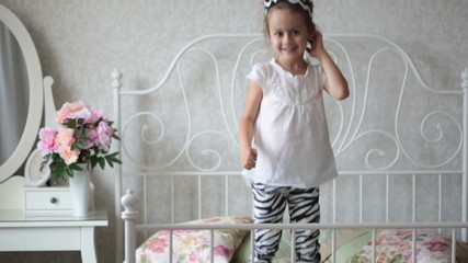 Little girl is jumping on the bed. HD video