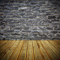 Wooden deck floor and brick wall