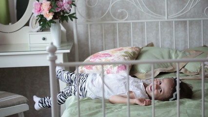 Little girl is jumping on the bed. FullHD video