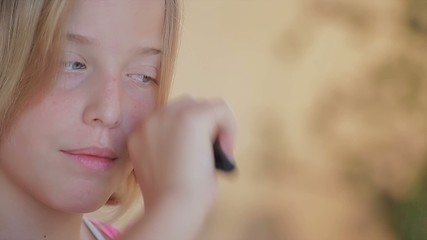 Little blond girl with blue eyes combing - close up