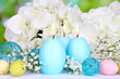 Leinwanddruck Bild - Easter candles with flowers on bright background