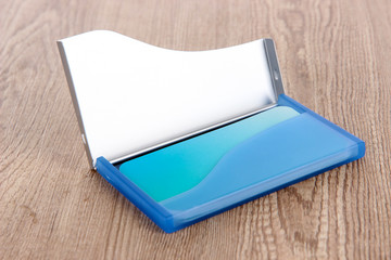 Blue business card holder on wooden background