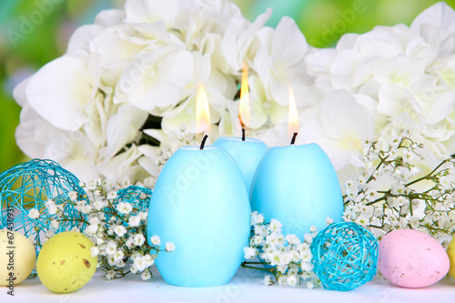 Leinwanddruck Bild Easter candles with flowers on bright background