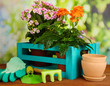 Beautiful flowers in pots on wooden table on natural background