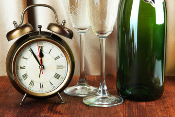 Alarm clock with champagne on table on golden cloth background